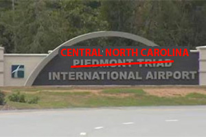 Sign at airport with Piedmont Triad crossed out, Central North Carolina instead