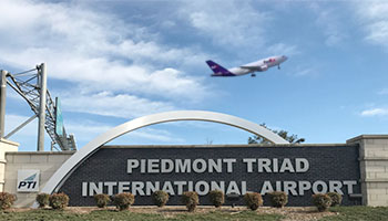 FedEx plane taking off over the sign at Piedmont Triad Airport
