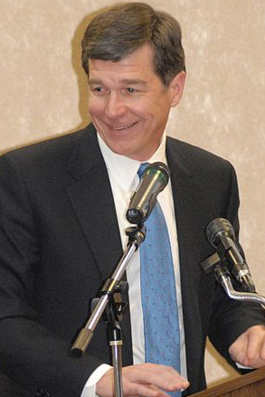 North Carolina Governor Roy Cooper speaking at a podium