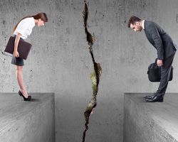 Two people staring into a chasm dividing them