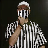 a football referee wearing a COVID-19 face mask, giving the hand gesture indicating a face mask penalty