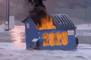 A dumpster on fire floating in floodwaters with the year 2020 on the front